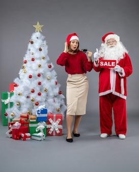 Vorderansicht des weihnachtsmannes mit weiblicher holdingbankkarte und verkaufsschrift auf der grauen wand