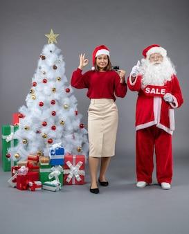 Vorderansicht des weihnachtsmannes mit weiblicher holdingverkaufsschrift und bankkarte an der grauen wand