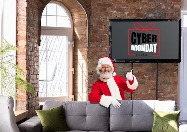 Vorderansicht des weihnachtsmanns, der auf den bildschirm mit cyber-montag-schriftzug in einem modernen zuhause oder büro zeigt. exemplar. schwarzer freitag, verkauf, finanzen, werbung, geld, finanzen, einkäufe. neujahr, weihnachten.