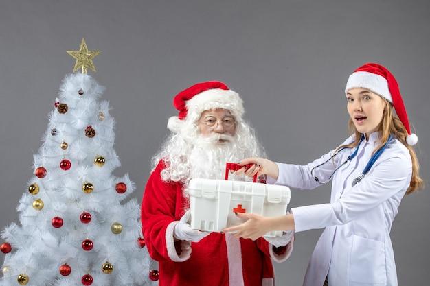 Vorderansicht des weihnachtsmanns mit der ärztin, die ihm erste-hilfe-kasten an der grauen wand gab