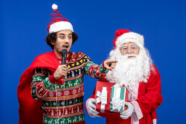 Vorderansicht des weihnachtsmanns mit einem jungen mann, der ein mikrofon an der blauen wand verwendet