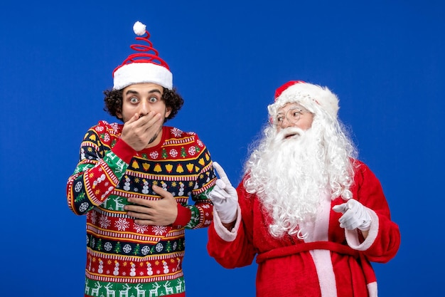 Vorderansicht des weihnachtsmanns mit jungem mann an der blauen wand