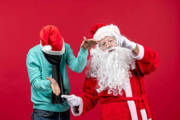 Vorderansicht des weihnachtsmanns mit jungem mann auf roter wand