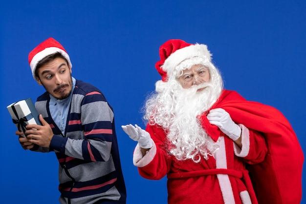 Vorderansicht des weihnachtsmanns mit jungem mann, der an der blauen wand präsent ist