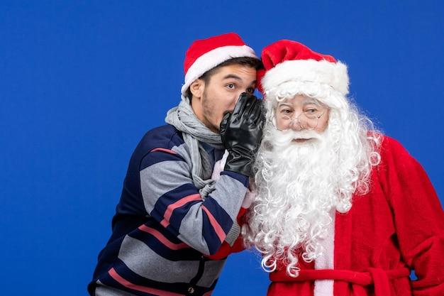 Vorderansicht des weihnachtsmanns mit jungem mann, der auf blauer wand flüstert