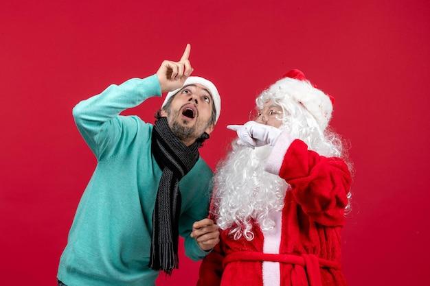 Vorderansicht des weihnachtsmanns mit jungem mann, der auf der roten wand posiert