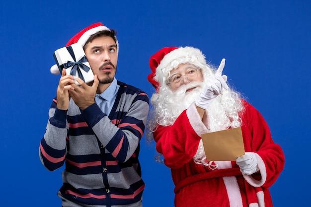 Vorderansicht des weihnachtsmanns mit jungem mann, der brief liest und geschenk an der blauen wand hält