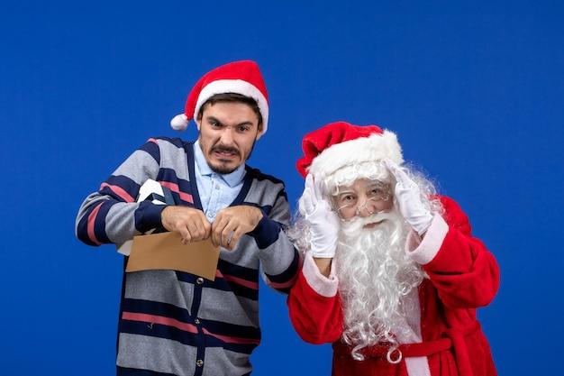 Vorderansicht des weihnachtsmanns mit jungem mann, der briefe an blauer wand zerreißt