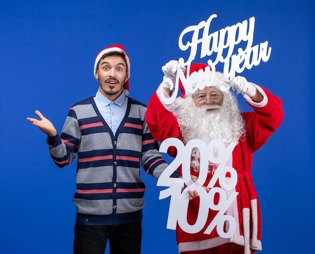 Vorderansicht des weihnachtsmanns mit jungem mann, der ein frohes neues jahr hält und die schriften an der blauen wand nummeriert