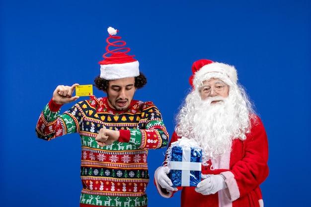 Vorderansicht des weihnachtsmanns mit jungem mann, der eine bankkarte hält und an der blauen wand präsent ist