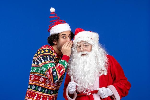 Vorderansicht des weihnachtsmanns mit jungem mann, der etwas an der blauen wand flüstert
