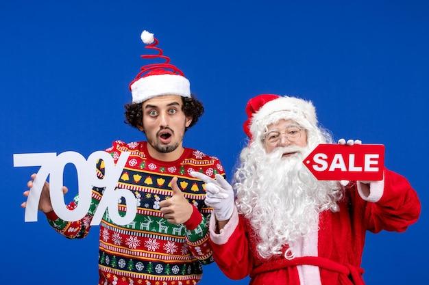 Vorderansicht des weihnachtsmanns mit jungem mann, der schriften an blauer wand hält und verkauft
