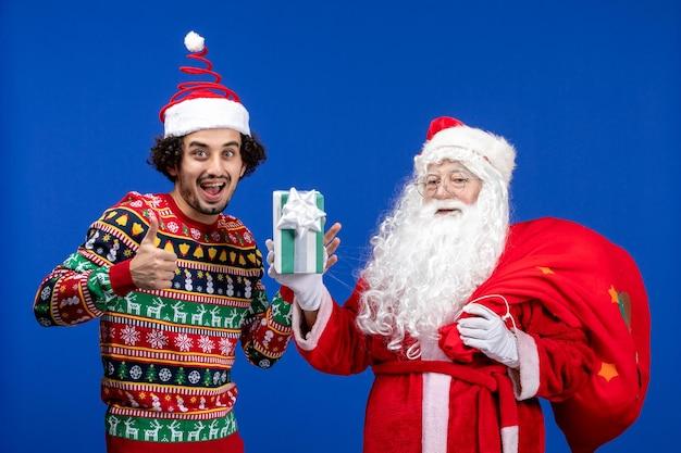 Vorderansicht des weihnachtsmanns mit jungem mann, der weihnachtsgeschenk an blauer wand hält