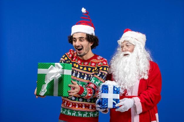 Vorderansicht des weihnachtsmanns mit jungem mann, der weihnachtsgeschenke an der blauen wand hält