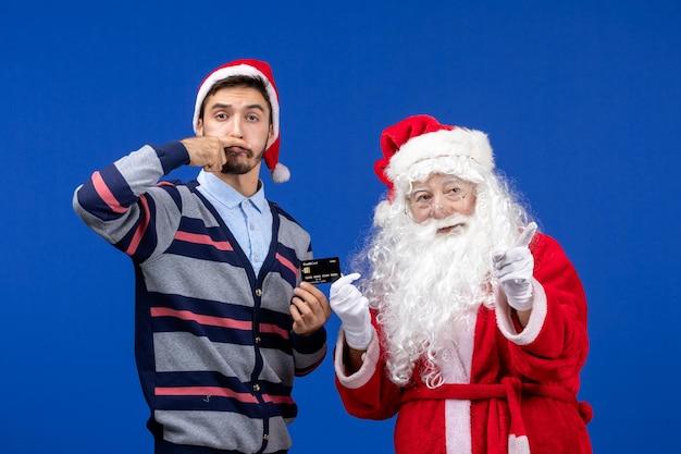 Vorderansicht des weihnachtsmanns mit jungem mann mit bankkarte an der blauen wand