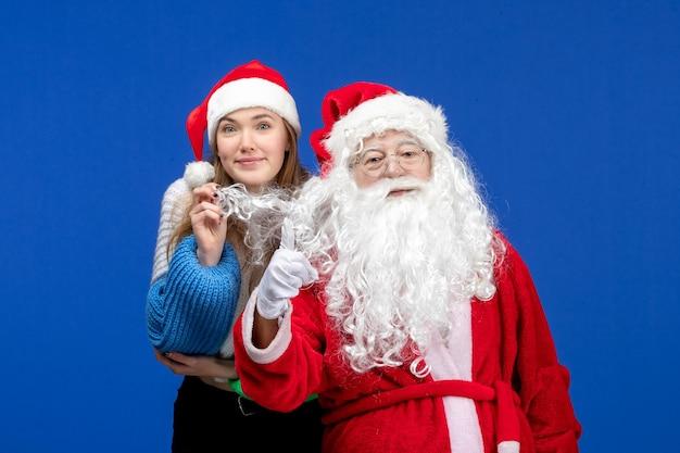 Vorderansicht des weihnachtsmanns mit junger hübscher frau an der blauen wand