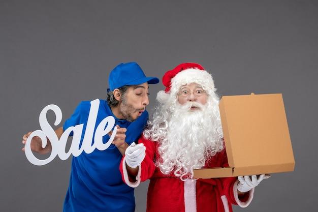 Vorderansicht des weihnachtsmanns mit männlichem kurier, der verkaufsfahne hält und nahrungsbox auf der grauen wand öffnet