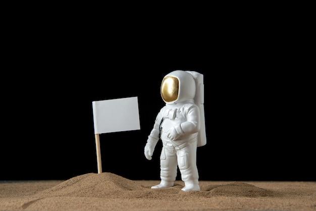 Vorderansicht des weißen astronauten mit weißer flagge auf schwarz