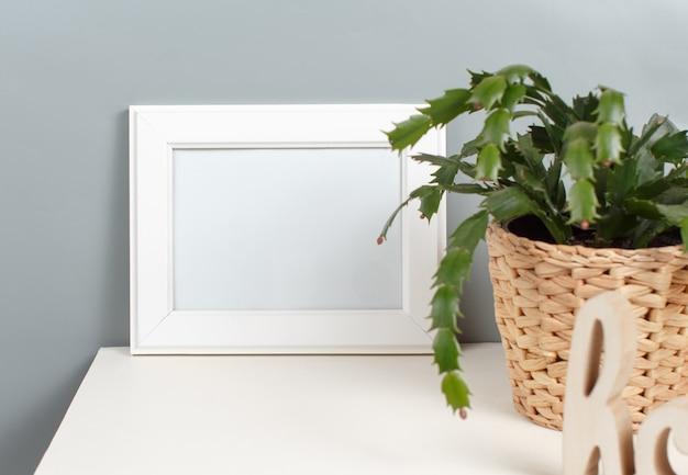 Vorderansicht des weißen plakatrahmenmodells mit pflanze in einem topf über der grauen wand