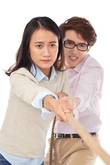 Vorderansicht des zugseils von zwei jungen asiatischen leuten, zum des wettbewerbs zu gewinnen