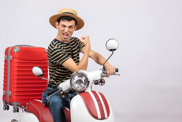 Vorderansicht des zuversichtlichen jungen mannes mit strohhut auf moped, das armmuskel zeigt