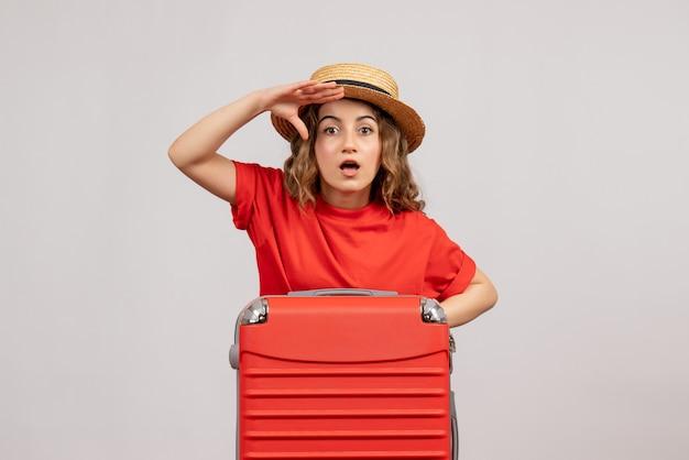 Vorderansicht, die das urlaubsmädchen mit ihrem kofferraum beobachtet