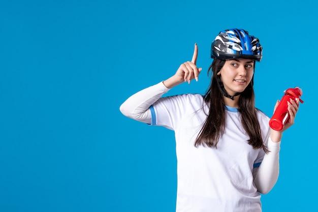 Vorderansicht, die junge frau in der sportkleidung mit helm auf blau aufwirft