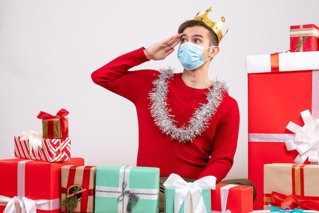 Vorderansicht, die jungen mann mit maske begrüßt, die auf bodenweihnachtsgeschenken sitzt