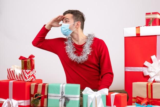 Vorderansicht, die jungen mann mit maske beobachtet, die um weihnachtsgeschenke sitzt