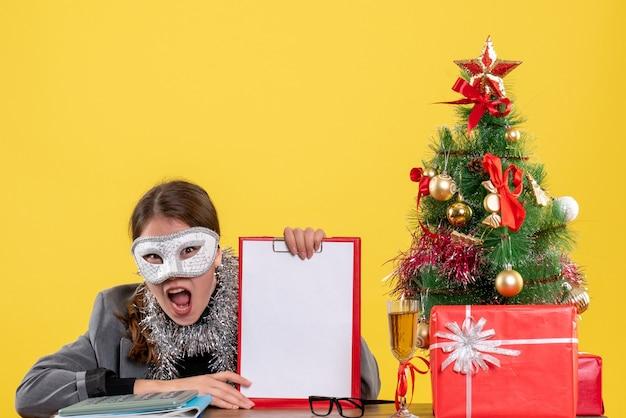 Vorderansicht, die junges mädchen mit maske schreit, die am tischweihnachtsbaum und geschenkcocktail sitzt