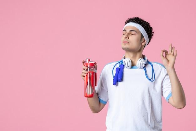 Vorderansicht, die männlichen athleten in sportkleidung mit flasche wasser meditiert