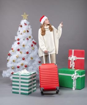Vorderansicht, die weihnachtsmädchen mit weihnachtsmütze zeigt, die die richtige richtung zeigt