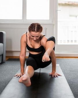 Vorderansicht, die yoga zu hause konzept praktiziert