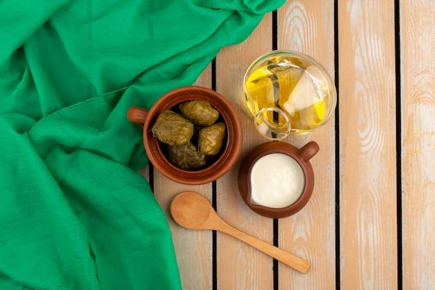 Vorderansicht dolma berühmte östliche mahlzeit mit hackfleisch im inneren zusammen mit joghurt und olivenöl auf dem braunen boden