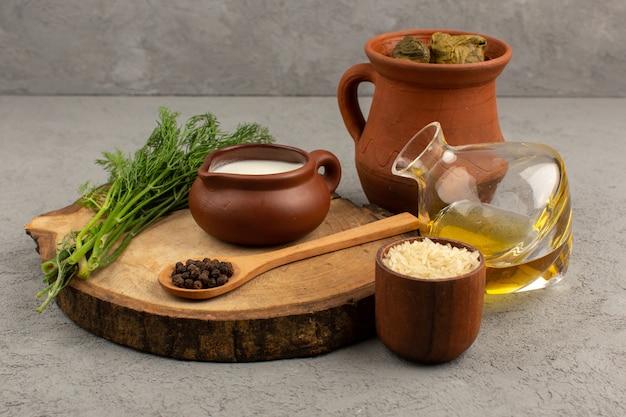 Vorderansicht dolma mit hackfleisch im inneren zusammen mit olivenöl und joghurt auf dem grauen boden