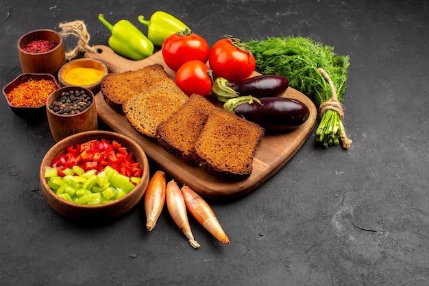 Vorderansicht dunkle brotlaibe mit gewürzen tomaten und auberginen auf dunklem hintergrund salat gesundheit reife mahlzeit gemüsediät