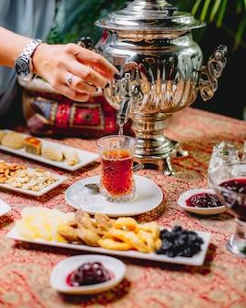 Vorderansicht eine frau gießt tee aus einer samowar-teekanne in ein glas armuda auf einer untertasse