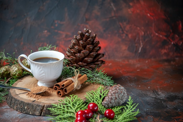 Vorderansicht eine tasse tee auf holzbrett zimtstangen kiefernzapfen auf dunkel