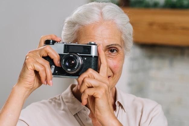 Vorderansicht einer älteren frau, die foto von der kamera macht