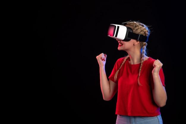 Vorderansicht einer aufgeregten jungen frau, die vr auf dunkler visueller ultraschall-spieltechnologie spielt