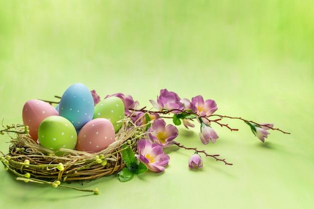 Vorderansicht einer bunten ostereier im nest und in den frühlingsblumen auf grünem hintergrund.