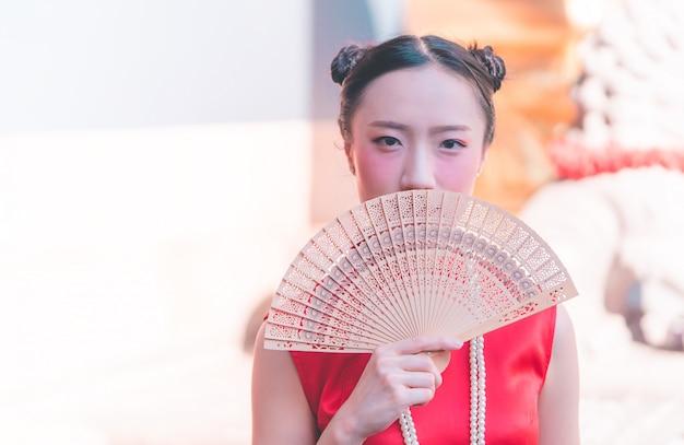 Vorderansicht einer chinesischen frau mit hölzernem fan im tempel