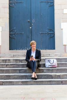 Vorderansicht einer eleganten lächelnden geschäftsfrau, die draußen auf treppe sitzt