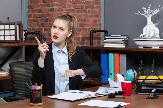 Vorderansicht einer emotional schockierten frau, die an einem tisch sitzt und im büro nach oben zeigt