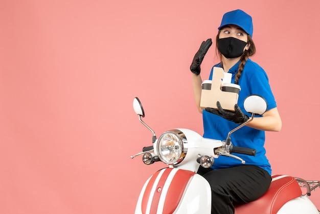 Vorderansicht einer fokussierten weiblichen lieferperson mit medizinischer maske und handschuhen, die auf einem roller sitzt und bestellungen auf pastellfarbenem pfirsichhintergrund liefert