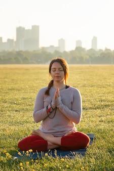 Vorderansicht einer frau, die draußen auf einer yogamatte meditiert