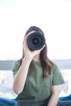 Vorderansicht einer frau, die durch kameraobjektiv schaut