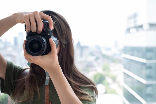 Vorderansicht einer frau, die fotos auf kamera macht