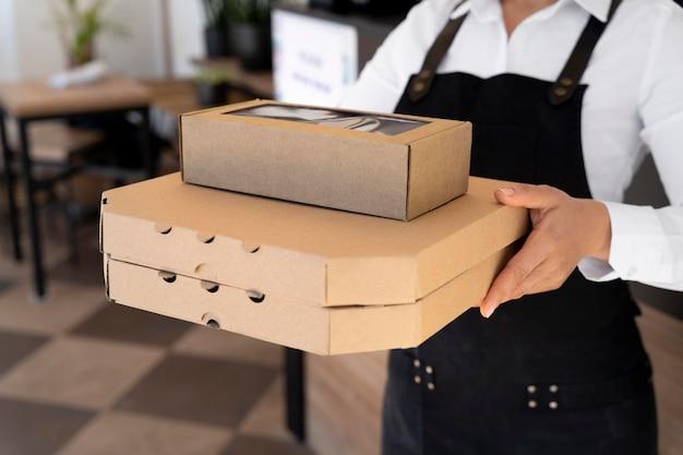 Vorderansicht einer frau mit schürze, die verpackte speisen zum mitnehmen hält