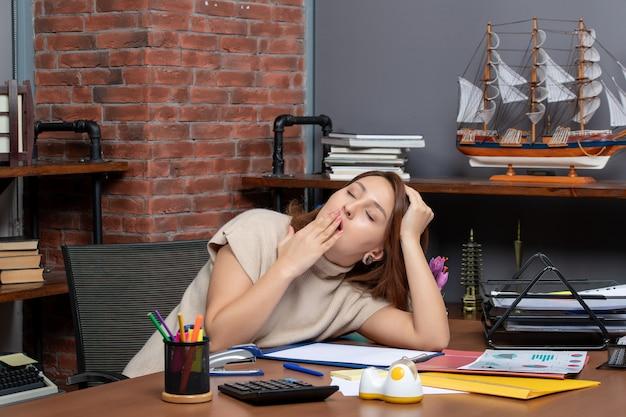 Vorderansicht einer gähnenden frau, die im büro arbeitet